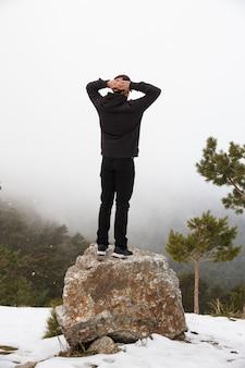 Homem caucasiano subiu em uma pedra em uma área de montanha de neve.