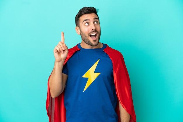 Homem caucasiano super-herói isolado em um fundo azul com a intenção de descobrir a solução enquanto levanta um dedo