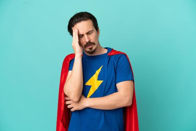 Homem caucasiano super-herói isolado em um fundo azul com dor de cabeça