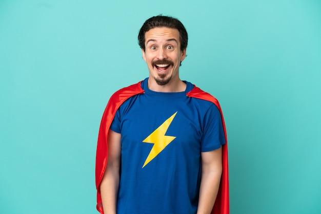 Homem caucasiano super-herói isolado em um fundo azul com expressão facial surpresa