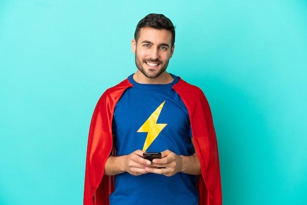 Homem caucasiano super-herói isolado em um fundo azul, enviando uma mensagem com o celular