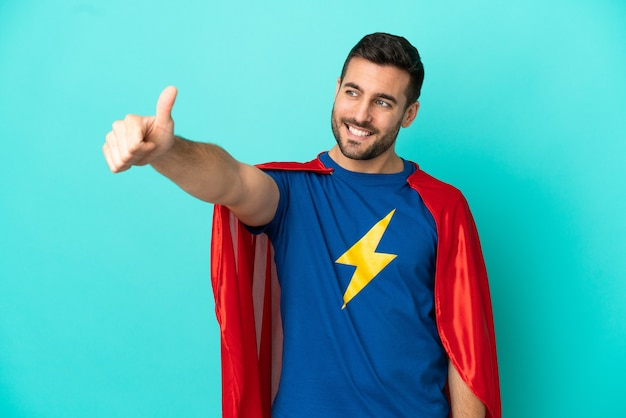 Homem caucasiano super-herói isolado em um fundo azul fazendo um gesto de polegar para cima