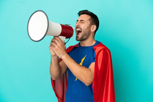 Homem caucasiano super-herói isolado em um fundo azul gritando em um megafone