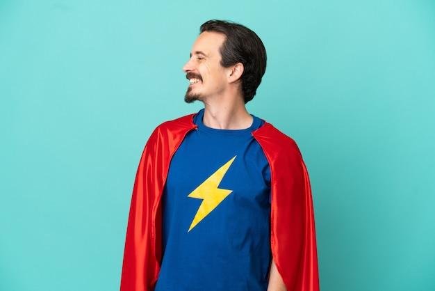 Homem caucasiano super-herói isolado em um fundo azul, olhando de lado