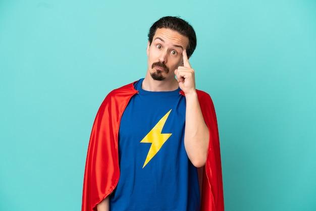 Homem caucasiano super-herói isolado em um fundo azul, pensando uma ideia