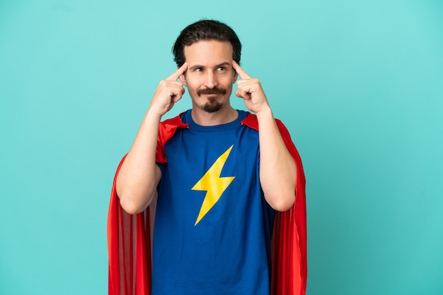 Homem caucasiano super-herói isolado em um fundo azul, tendo dúvidas e pensando