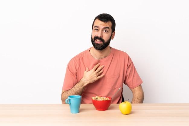 Homem caucasiano tomando café da manhã em uma mesa apontando para si mesmo.