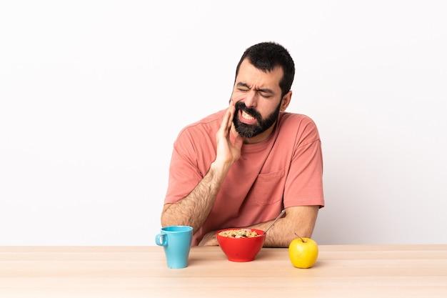 Homem caucasiano tomando café da manhã em uma mesa com dor de dente