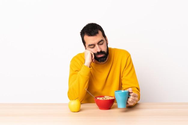Homem caucasiano, tomando café da manhã em uma mesa com expressão cansada e entediada