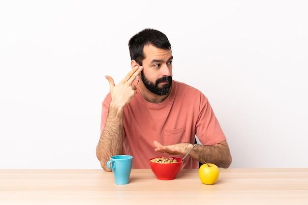 Homem caucasiano tomando café da manhã em uma mesa com problemas para fazer o gesto de suicídio.