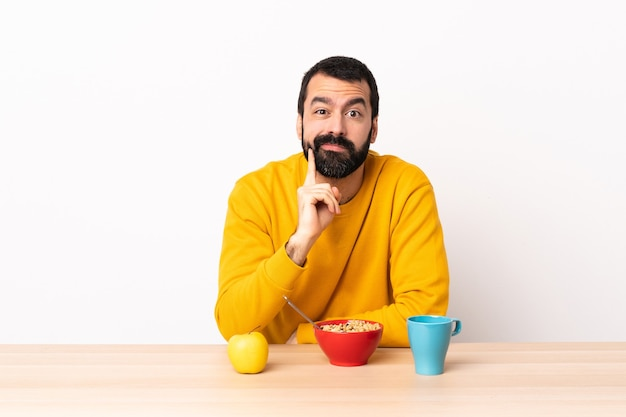 Homem caucasiano tomando café da manhã em uma mesa e pensando.