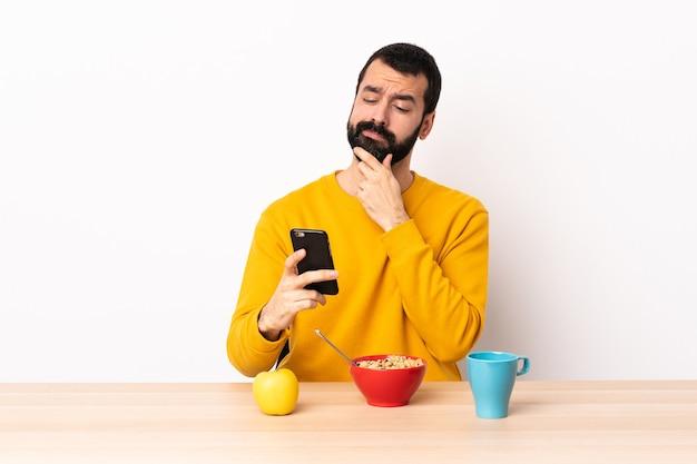 Homem caucasiano tomando café da manhã em uma mesa pensando e enviando uma mensagem.