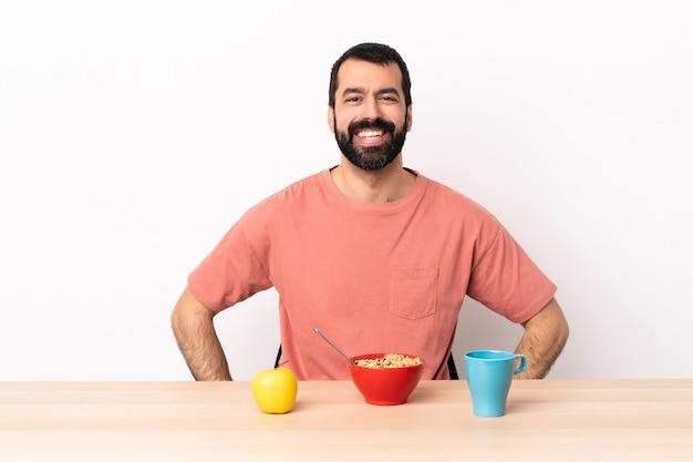 Homem caucasiano tomando café da manhã em uma mesa, posando com os braços no quadril e sorrindo.