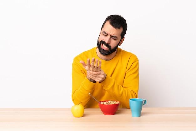 Homem caucasiano, tomando café da manhã em uma mesa que sofrem de dor nas mãos