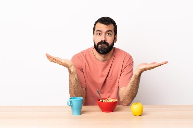 Homem caucasiano tomando café da manhã em uma mesa, tendo dúvidas ao levantar as mãos.