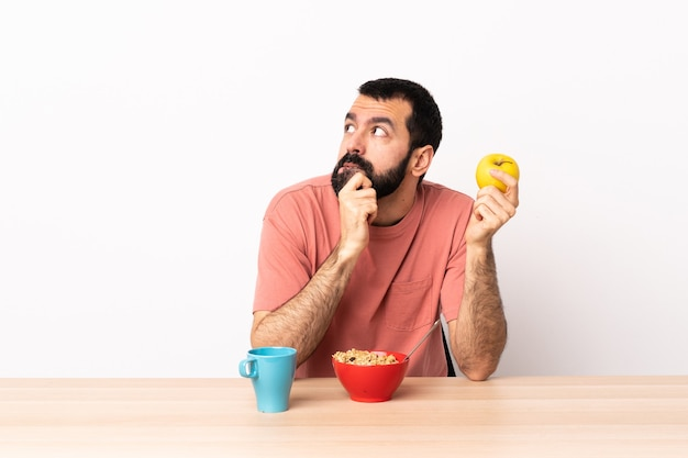 Homem caucasiano tomando café da manhã em uma mesa, tendo dúvidas e com expressão facial confusa.