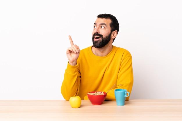 Homem caucasiano tomando café da manhã em uma mesa, tendo uma ideia apontando o dedo para cima.