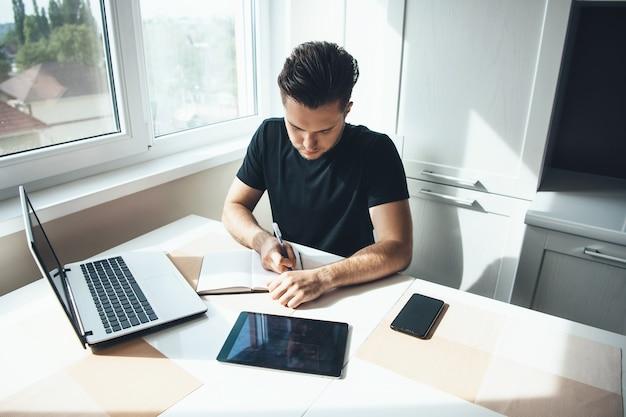 Homem caucasiano trabalhando no laptop em casa, escrevendo algo