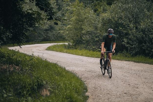 Homem caucasiano usando bicicleta preta para treinamento ao ar livre