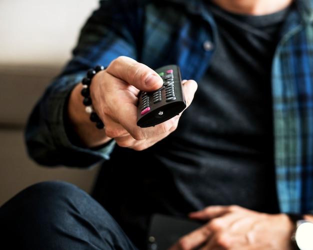 Homem caucasiano, usando, tv, controle remoto