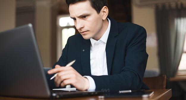 Homem caucasiano vestido de terno está trabalhando duro no computador branco usando uma caneta e um livro