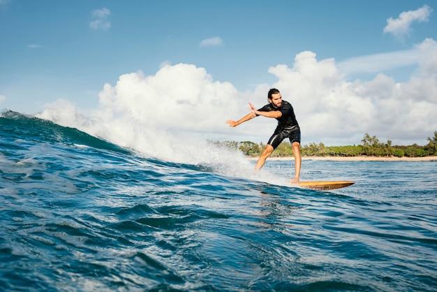 Homem cavalgando sua prancha de surfe e se divertindo, tiro longo