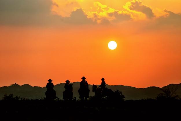 Homem cavalo no campo contra o pôr do sol