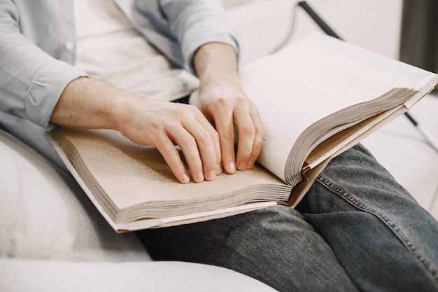 Homem cego lendo livro braille no sofá. pessoas com deficiência