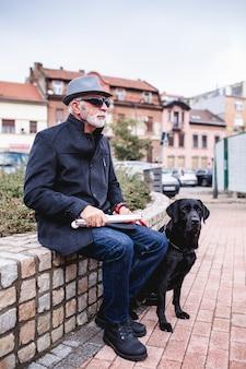 Homem cego maduro com seu cão-guia sentado na rua.