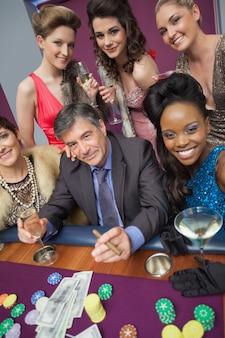 Homem cercado por mulheres bonitas na mesa de roleta
