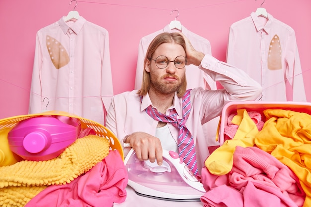 Homem cercado por uma pilha de roupas lavadas e passando roupas segurando a mão na cabeça usa óculos redondos, camisa e gravata