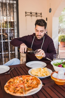 Homem, cerveja derramando, em, vidro, sentando tabela