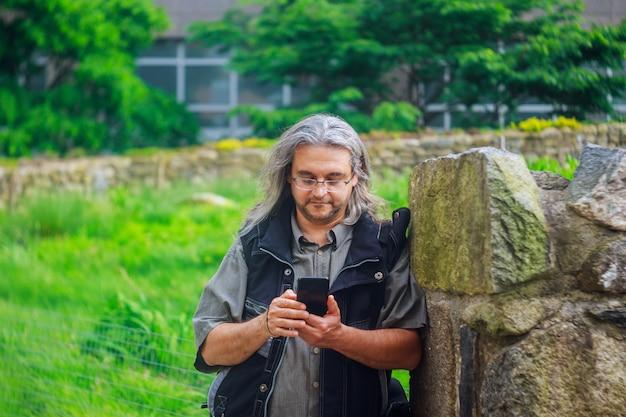 Homem chamando com telefone móvel está chamando por telefone celular na rua
