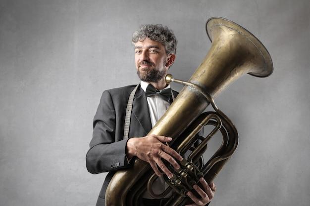 Homem charmoso com uma tuba