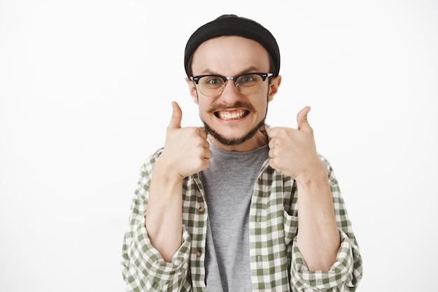 Homem charmoso satisfeito e satisfeito, divertido, com barba nos óculos e gorro preto sorrindo alegremente mostrando os polegares para cima em um gesto semelhante
