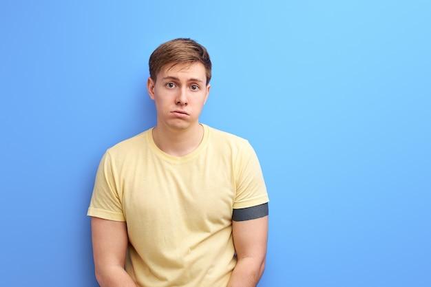 Homem chateado em pé e olhando para a câmera com cara de tristeza insatisfeita, estúdio interno, isolado em um fundo azul, retrato