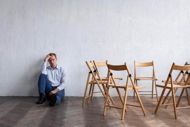 Homem chateado em sessão de terapia de grupo com cadeiras vazias