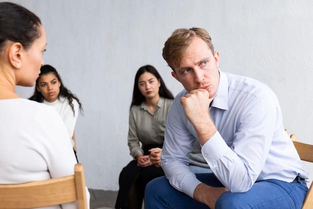 Homem chateado em sessão de terapia de grupo