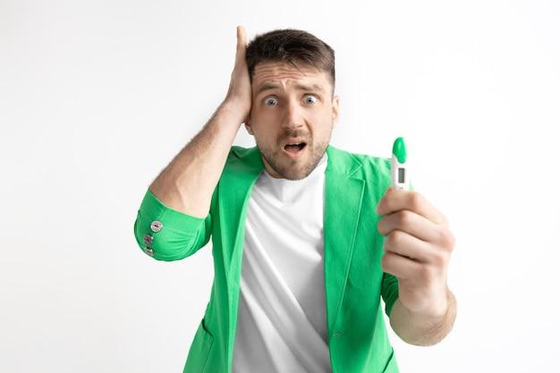 Homem chateado, procurando no teste de gravidez.