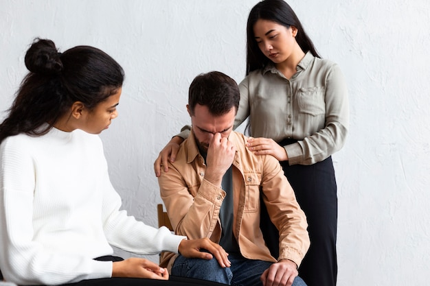 Homem chateado sendo consolado em sessão de terapia de grupo