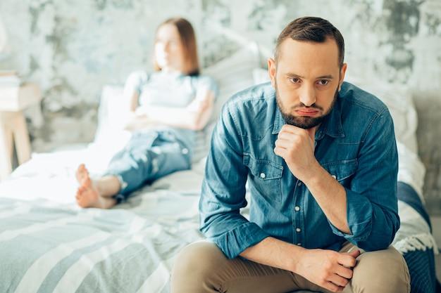Homem chateado sentado na cama com uma mulher ofendida ao fundo e pensando em divórcio