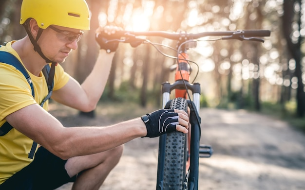 Homem checando a pressão do pneu na roda da bicicleta durante um passeio na floresta