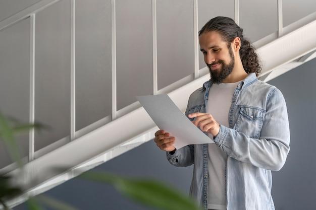 Homem checando algumas anotações no trabalho