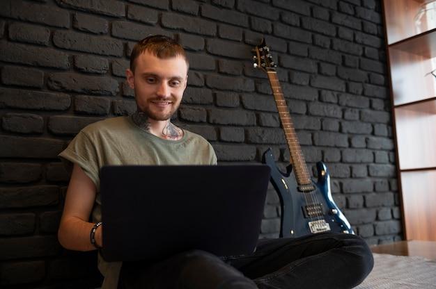 Homem checando seu laptop ao lado de sua guitarra