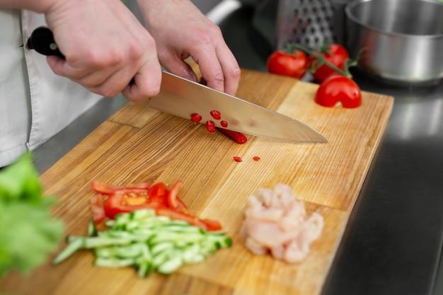 Homem chef cortando pimenta na mesa