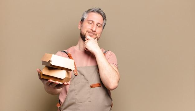 Homem chef de meia-idade com hambúrgueres. conceito de churrasco
