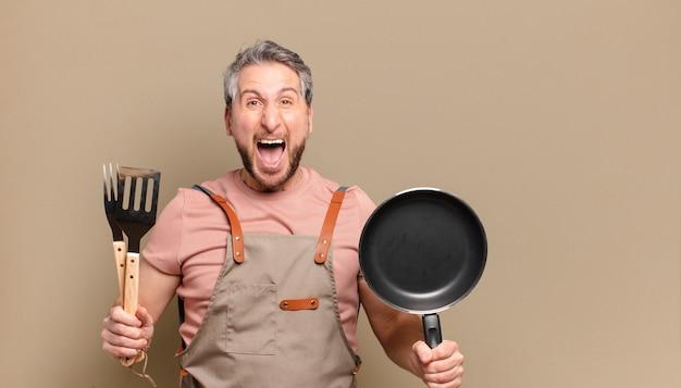 Homem chef de meia idade. placa de churrasco