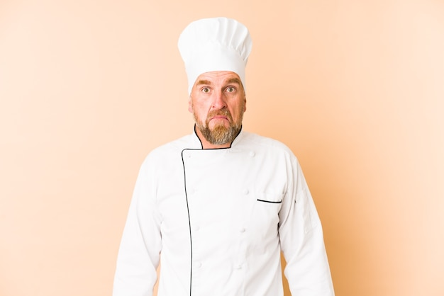 Homem chef isolado em bege encolhe os ombros e abre os olhos confusos.