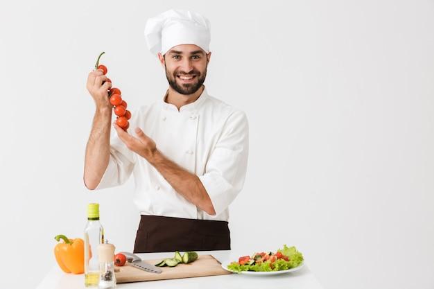 Homem chefe caucasiano de uniforme segurando tomates enquanto cozinha salada de legumes na tábua de madeira isolada sobre a parede branca