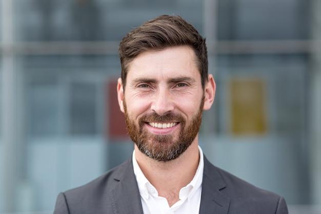 Homem chefe olhando para a câmera e sorrindo, jovem empresário banqueiro com foto de barba com retrato de perto